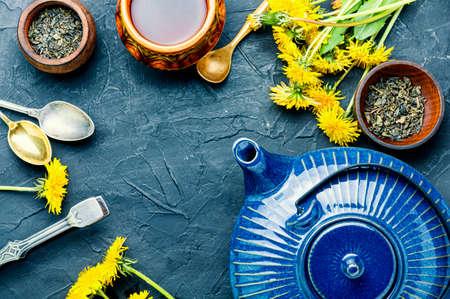 Ceramic teapot with herbal tea from flowering dandelions.Herbal tea from dandelions