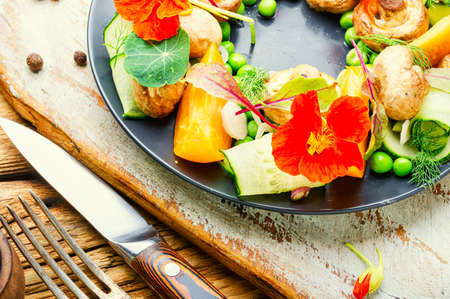 Summer vegetable salad decorated with nasturtium flowers.Healthy vegetarian food Stock Photo