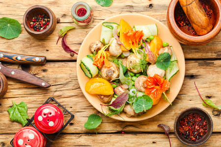 Salad with stewed mushrooms,cucumber,tomato and nasturtium.Spring diet salad Stock Photo