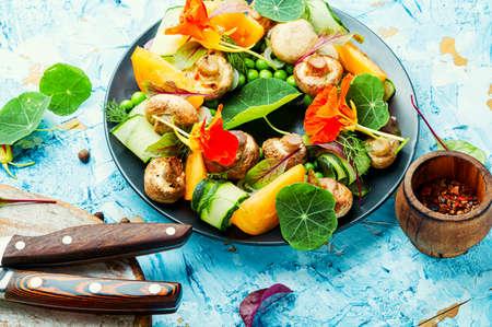 Salad with stewed mushrooms, cucumber,tomato and nasturtium.