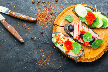 Summer bruschettas or canape with cream cheese,bacon and vegetables.Traditional italian bruschetta