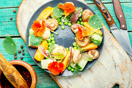 Summer vegetable salad decorated with nasturtium flowers.Healthy vegetarian food Reklamní fotografie