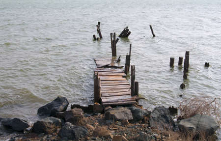 Destruction of the old wooden bridge in the water with strong waves