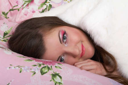 Young girl resting in a bed with pink flowers