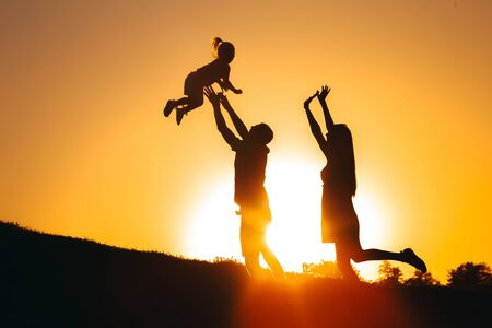 A father tosses his daughter at sunset on a hill, and next to them her mother rejoices