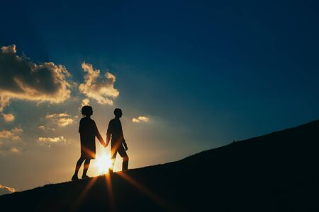 Couple in love at sunset on a background of blue sky and clouds rises on a hill
