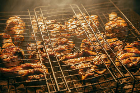 A few pieces of chicken meat is grilled on coals, on a barbecue