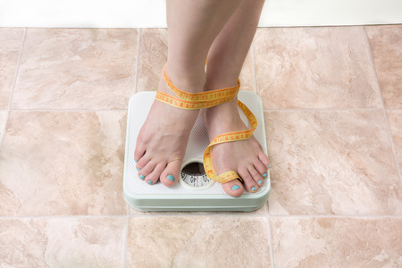 underweight: image of woman standing on a weight scale