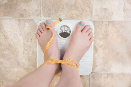 human toe: image of woman standing on a weight scale