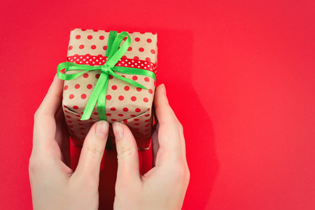 Present in woman hand on red background.
