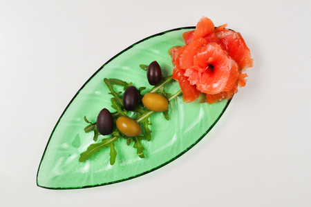Salmon slices on a plate with salt and olives isolated on white.