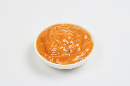 Orange sauce in white plate on white background.