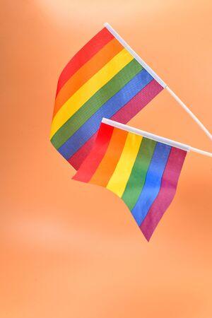 LGBT flag on orange background. Copy space.