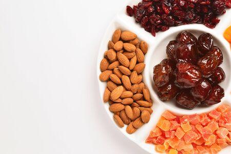 Mix di frutta secca e noci. Albicocca, uva passa, mirtillo rosso, datteri frutta. Isolato su uno sfondo bianco. Spazio per testo o design.