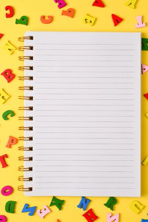 Open empty notebook and colorful letters on a yellow background. Top view. Space for text or design.