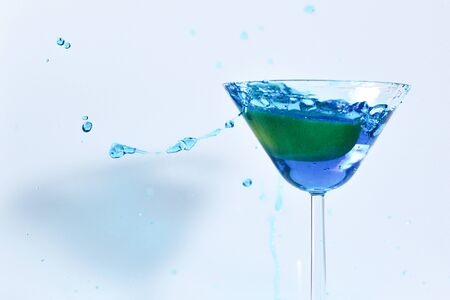 Cocktail with blue liquid in glass. Glass with blue water pouring with liquid with splashes and drops. Martini glass filling with alcohol with splashes on white background. Refreshing drink concept.