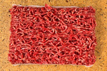 Chopped raw meat  on wooden background.