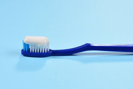 Toothbush with toothpaste on a blue background. Фото со стока