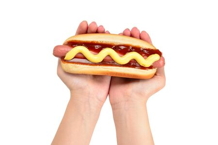 Hot dog in woman hand isolated on white background. Copy space.