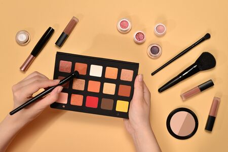 Eye shadow palette on woman hand. Professional makeup products with cosmetic beauty products, foundation, lipstick,  eye shadows, brushes and tools.
