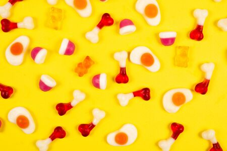 Assorted jelly sweets on yellow background. Pattern. Banco de Imagens