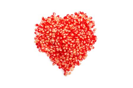 Pomegranate red seeds isolated on white. Heart symbol.