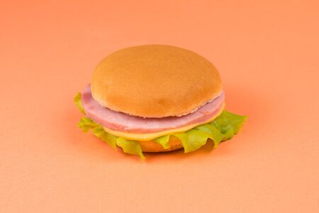 Sandwich with ham, cheese, lettuce on orange background. Space for text or design.