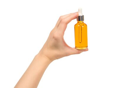 Bottle with oil in woman hand isolated on white. Copy space.