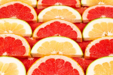 Pomelo and grapefruit juicy slices background. Stock Photo