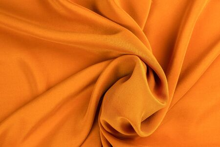 Golden silk or satin luxury fabric texture can use as abstract background. Top view. Zdjęcie Seryjne
