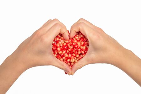 Woman hold pomegranate seeds. Heart symbol, isolated on white. Stok Fotoğraf