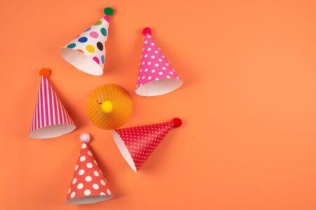 Colorful birthday caps on orange background. Top view. Foto de archivo - 135388215