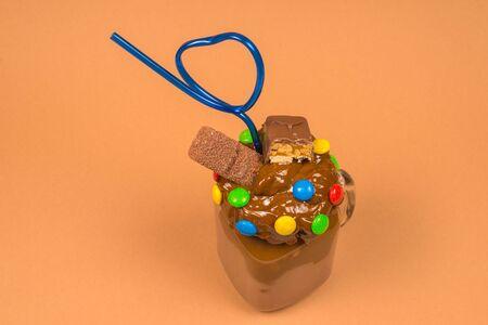 Chocolate milkshake with whipped cream, cookies, waffles, served in glass mason jar.