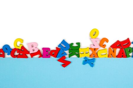 Row of multicolored letters isolated on a white background. Copy space. Frame.