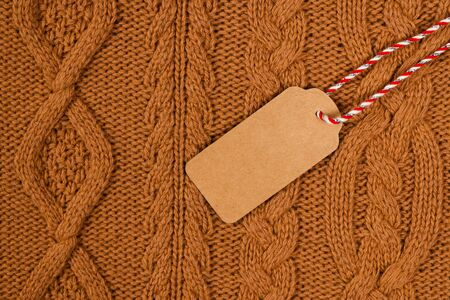 Brown tag on brown knitted sweater. Copy space. 版權商用圖片