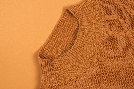 Warm brown knitted sweater on brown background. Copy space.