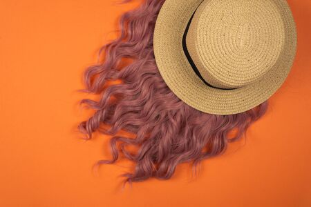Summer hat lay on pink hair on orange background. Copy space.