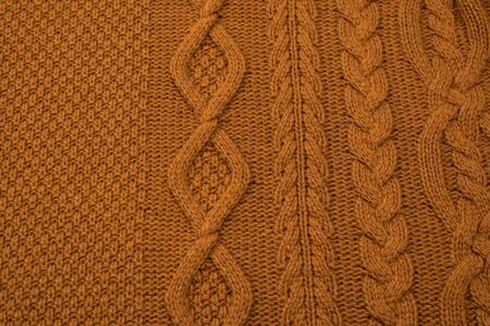 Brown knitted fabric pattern. Warm clothes.