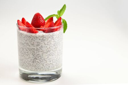 Chia pudding with strawberry and mint on a white background. Space for text or design.