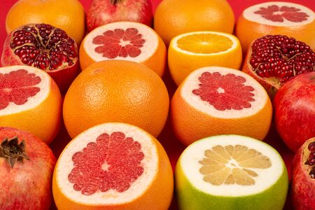 Juicy grapefruit, orange, pomegranate, citrus sweetie on red background.