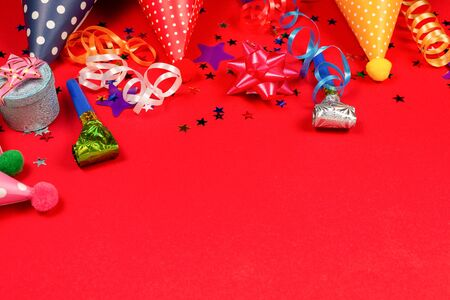 Festive golden and purple stars of confetti  and a present, birthday caps on a red background. Space for text or design.