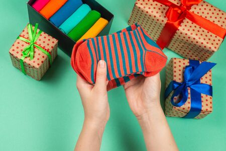 Colorful collection of cotton socks as a gift in woman hands. Gift. Foto de archivo - 138465288