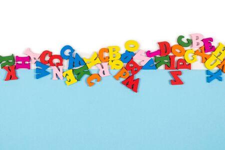 Rangée de lettres multicolores isolées sur fond blanc. Espace de copie. Cadre.