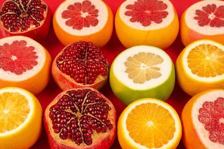 Pamplemousse juteux, orange, grenade, bonbon aux agrumes sur fond rouge.
