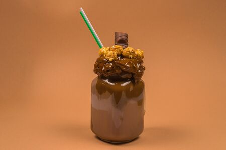 Chocolate milkshake with whipped cream, cookies, waffles, served in glass mason jar. Freak or crazy sweet shake. Space for text or design.