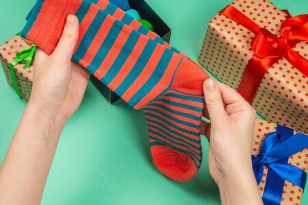 Colorful collection of cotton socks as a gift in woman hands. Gift. Banco de Imagens