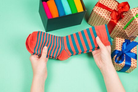 Colorful collection of cotton socks as a gift in woman hands. Gift. Reklamní fotografie