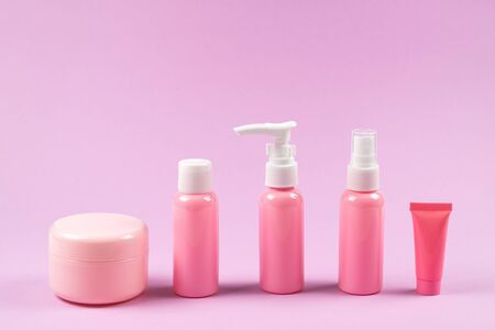 Pink plastic bottles for hygiene products, cosmetics, hygiene products on a pink background. Copy space.