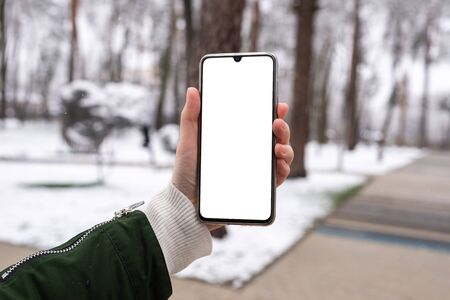 Smart phone in woman hands in winter park.  White screen. Copy space.