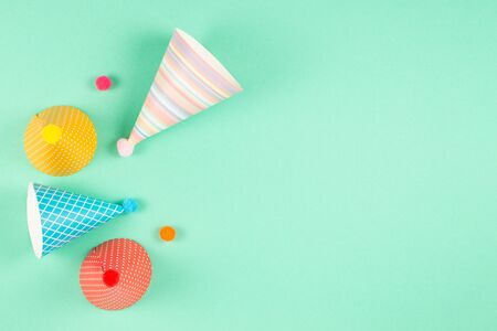 Colorful birthday caps on mint background. Top view. Foto de archivo